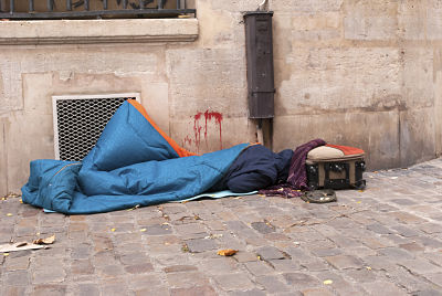 Homeless man is sleeping on the street next to wall with blood stains; people and poverty concept.